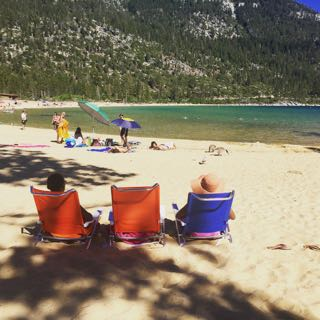 Image of two women on beach chairs looking into Lake Tahoe lounging on the beach.