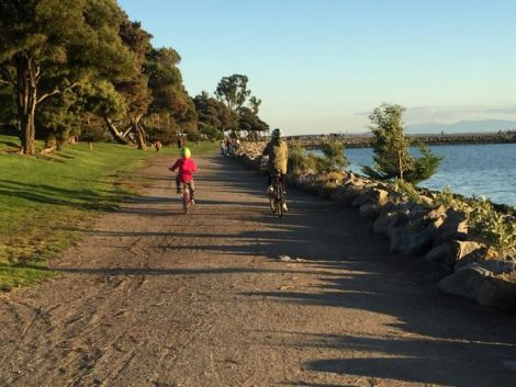 Image of two children riding bikes by the water with a fall backdrop