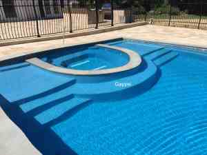 gunite swimming pool with spill-over spa, sundeck , patio and outdoor kitchen