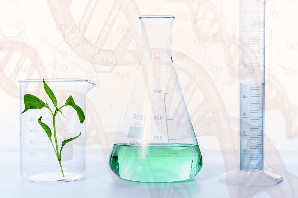 A plnt in a jar, a vile of light green liquid of unknown origin, and a beeker full of a second unknown liquid, light blue in color, all sit on a table. A DNA strand is the backdrop for the image.