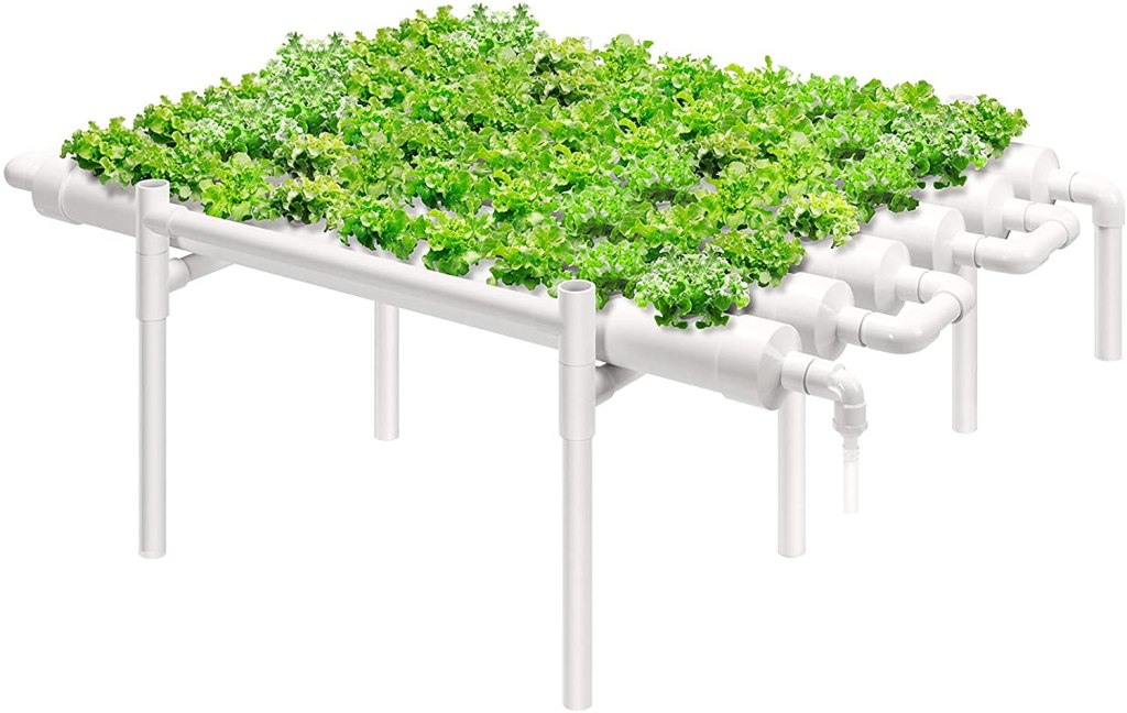 A glossy white one-level ebb and flow hydroponics sytem growing lettuce in 6 PVC pipes.