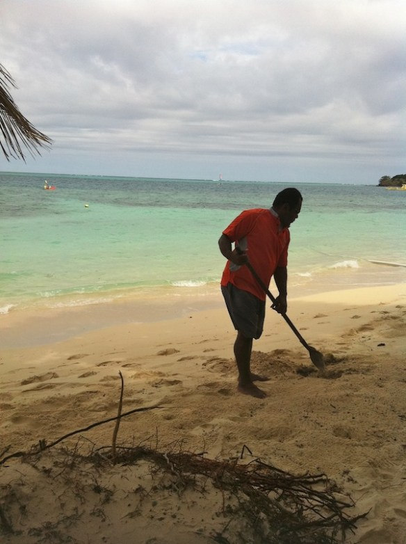 Fijian man grooming beach