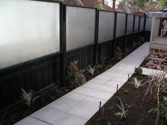 Timber and perforated steel screen with newly planted garden