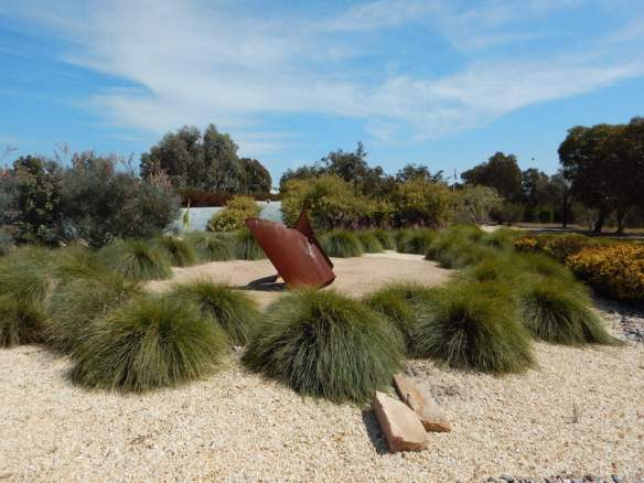 Tufts of lomandra surrounds one of the rusty sculptures