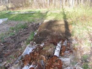 Hugelkultur bed half completed, more soil needed.