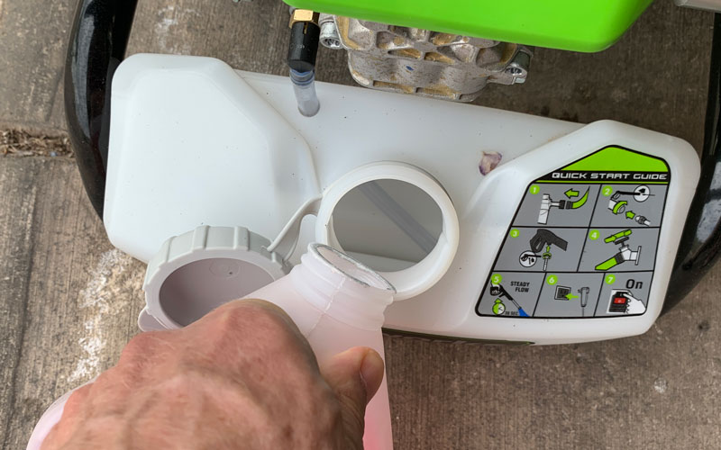 Greenworks-1800-PSI-Pressure-Washer-pouring-in-soap