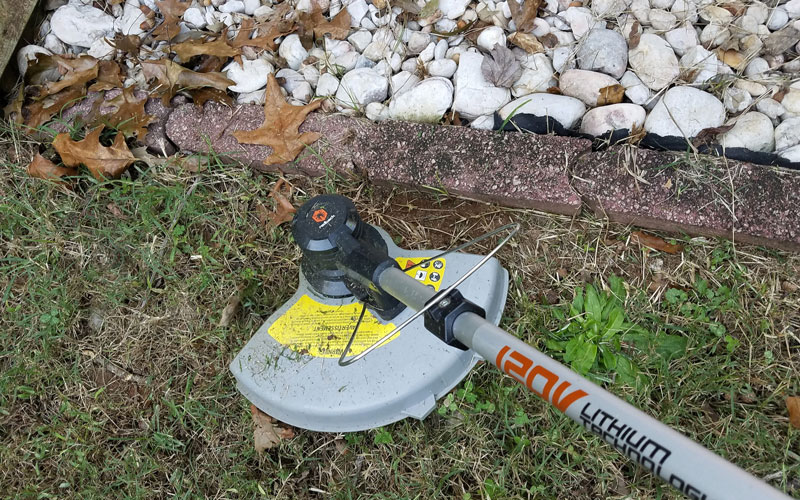 Redback-120v-String-Trimmer-trimming-against-pavers-15
