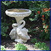 Ornate concrete birdbath with duck statues at the base