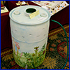 Rain barrel painted with an outdoor scene