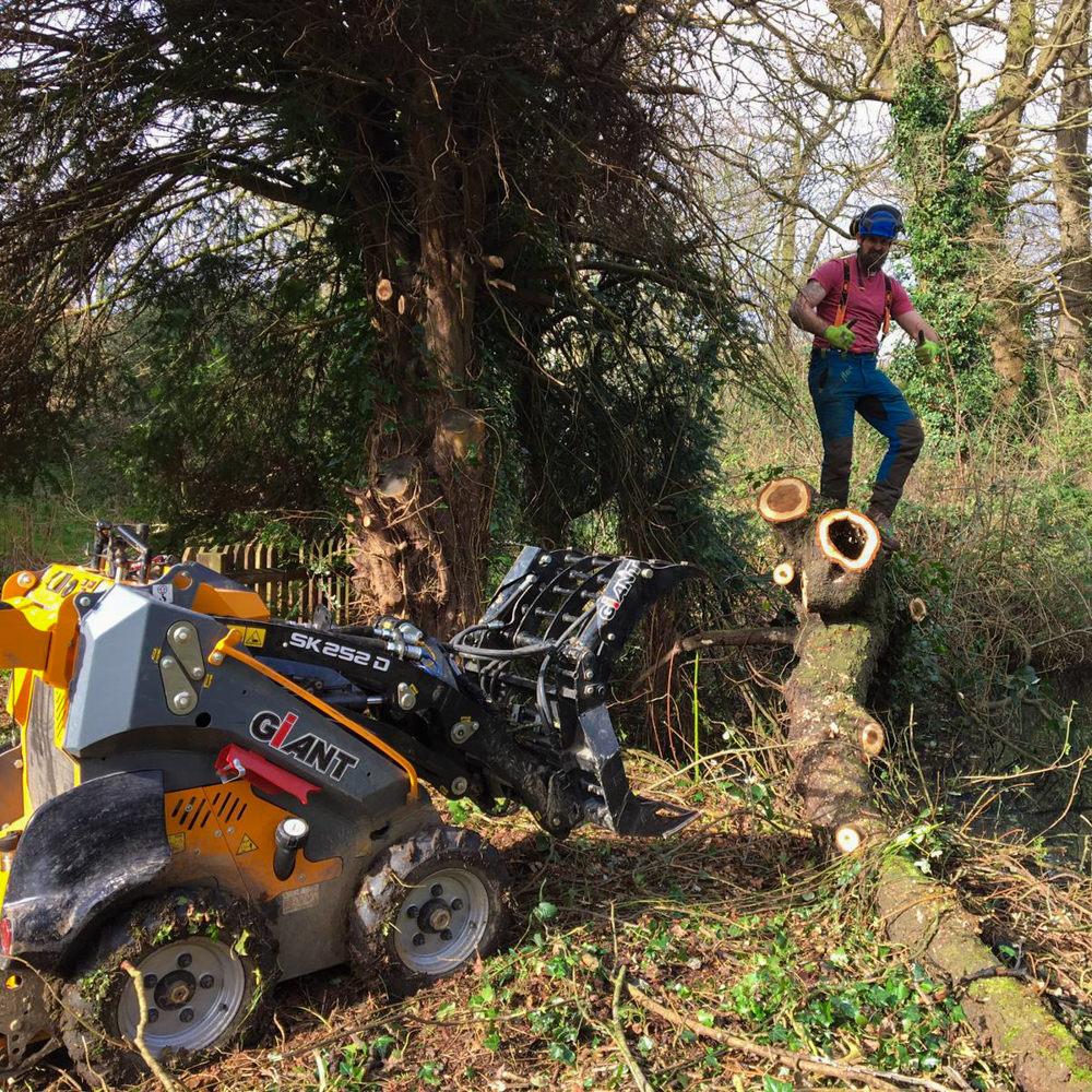 Garden Knight team member Andrew posing with the grab which is used for lifting heavy tree trunks