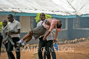 """""""Teargas canisters were thrown outside our class room- Kibera student"""". Willis is seen in this photo carrying one of his fellow students Photo :Katie G. Nelson"""