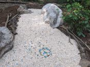 A visitor has created a peace sign in the river rock installation.
