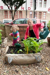 Ellie and Daughter watering their veg in their front garden
