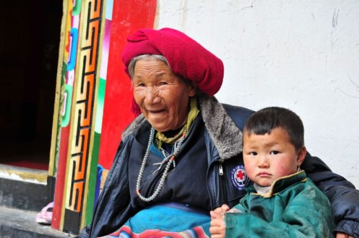 A woman minds her great-grandson in a small village near Baima Mountain