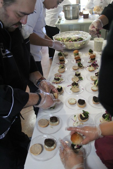 Instructor Brian Tatsukawa with students from Navajo Technical College assembling buffalo sliders with green chili and jalapeño mayo, kale slaw with a citrus vinaigrette, and a blue corn Rosemary bun (photo by Elizabeth Hoover).