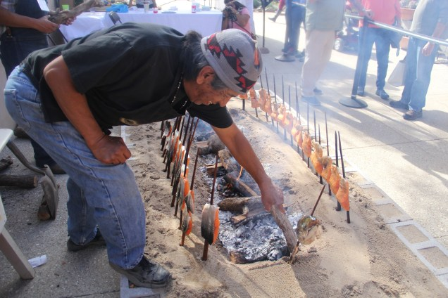 Ed Mata, roasting salmon over the fire. Photo by Elizabeth Hoover