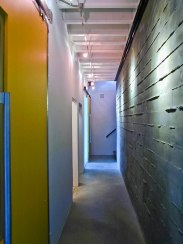 Lower level hall, board form concrete wall & rolling doors