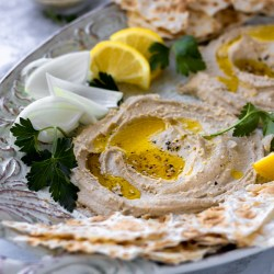 healthy hummus on a white plate with olive oil