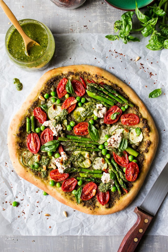 white board with cup of pesto and vegetable pizza with basil and asparagus