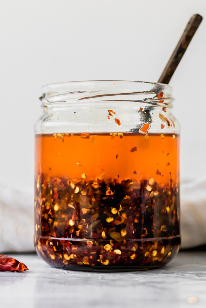 glass jar of chile oil with wooden spoon inside