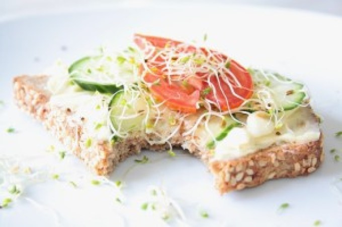 raw garlic on toast with fresh tomato, cucumber and sprouts without a bite
