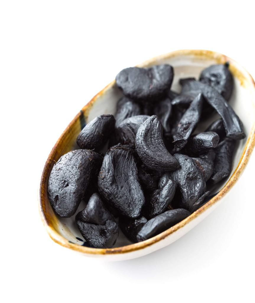 Everything you need to know about delicious and healthy black garlic - how it tastes like, how to make it, cook with it, plus recipes.