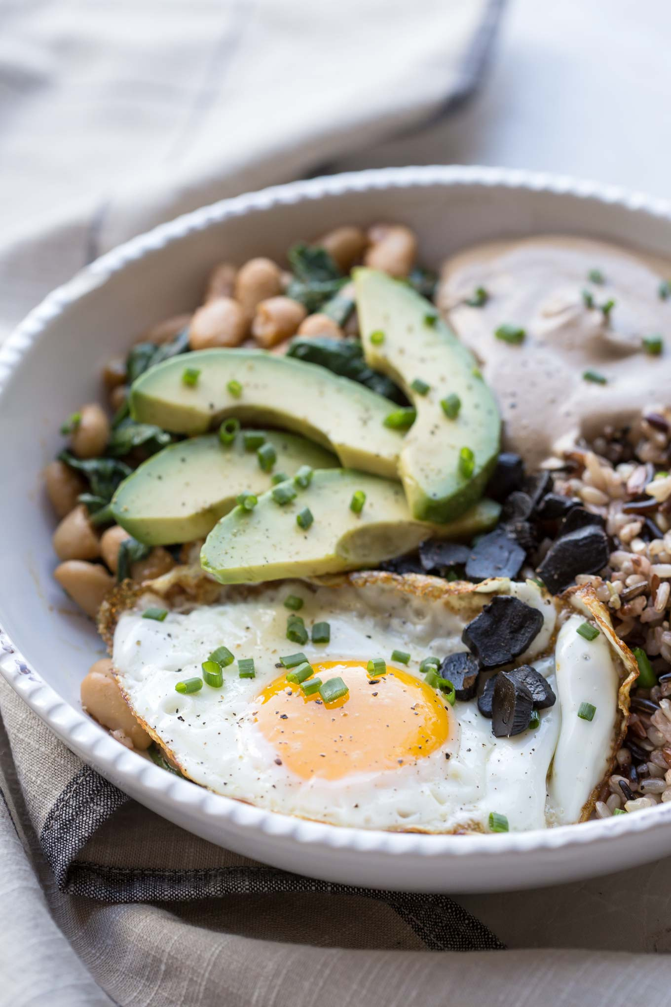 Protein Bowl with Cashew Black Garlic Sauce, Fried Egg, Beans and Avocado in a Creamy Bowl - 45 degree view