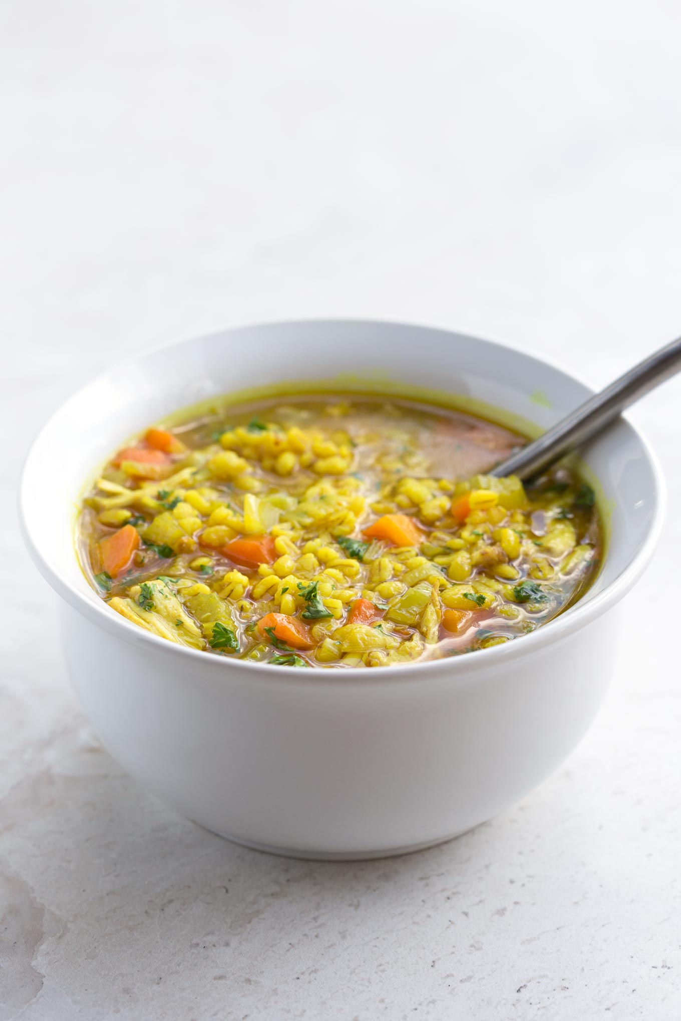 Chicken Soup with Barley and Turmeric in a White Serving Bowl - 90 degree view