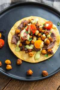 Black Plate with Crispy Chickpea Tostadas and garnished with tomatoes and avocado drizzle