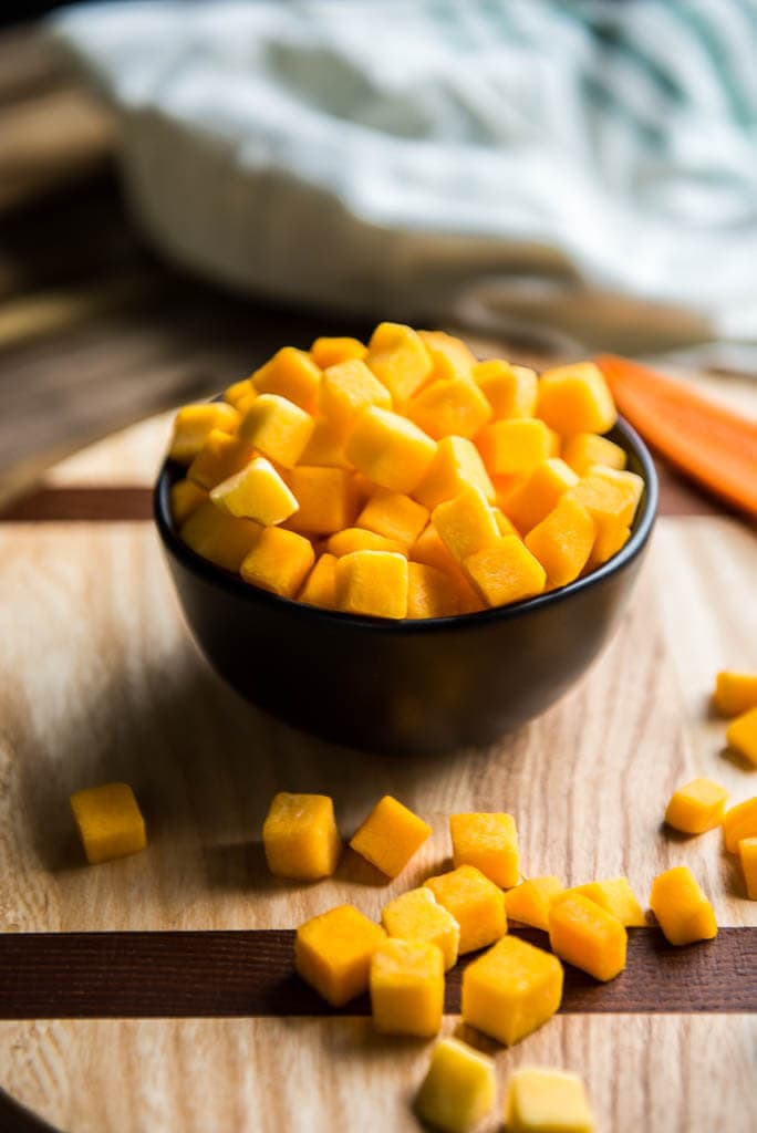 Small black bowl filled with cubed butternut squash on cutting board for Butternut Squash Minestrone