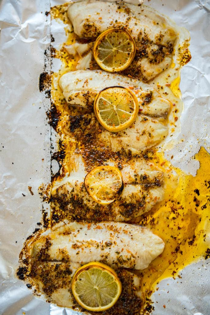 Baked Lemon Butter Tilapia on foil lined baking sheet lightly browned and ready to serve