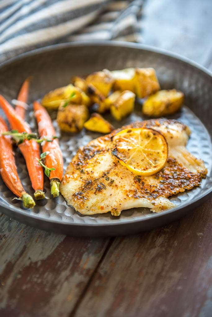 Baked Lemon Butter Tilapia on metal plate served with potatoes and carrots