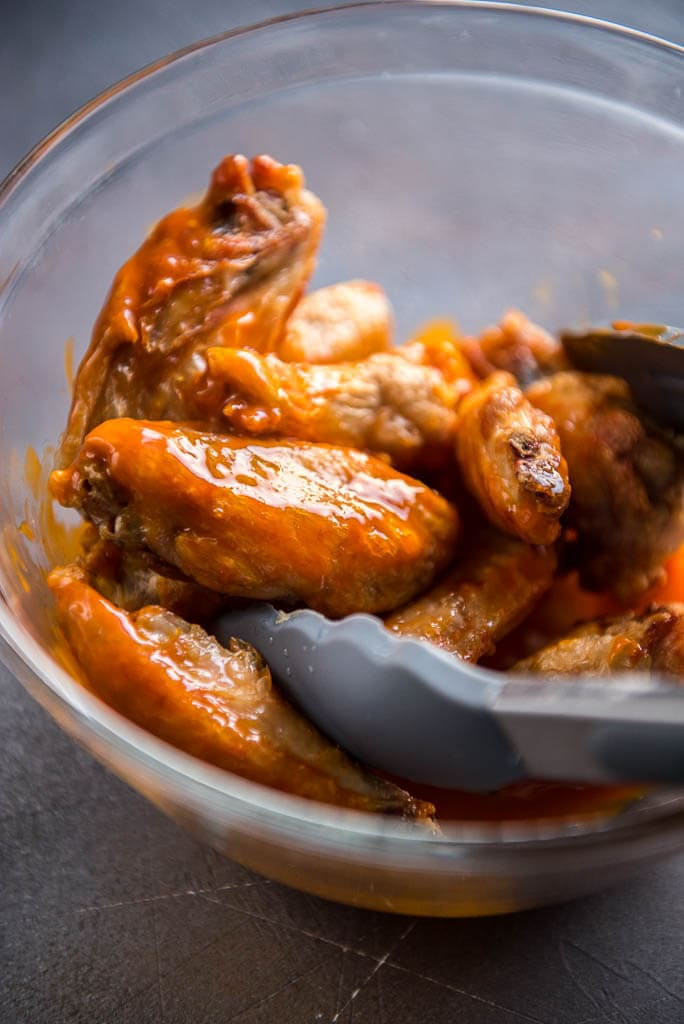 Air Fryer Chicken Wings being tossed with sauce in glass bowl using tongs