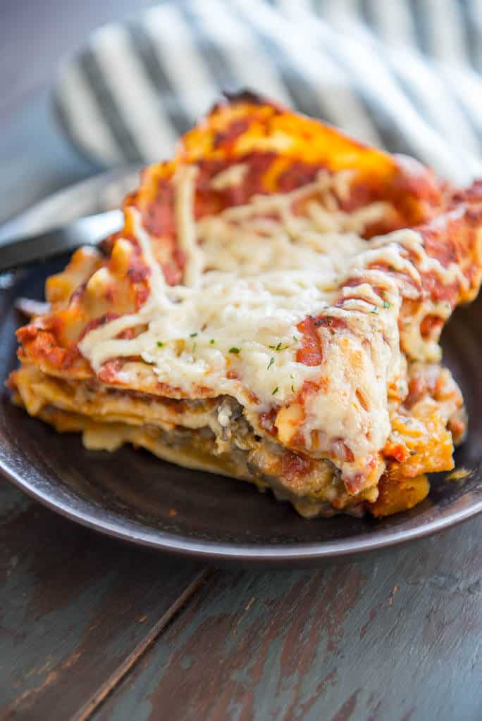 Vegan Lasagna on a brown plate with a gray striped napkin