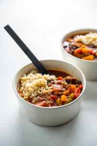 stuffed pepper soup in white bowl topped with brown rice on white counter