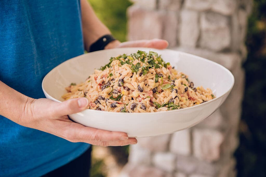 southwest pasta salad in white bowl being carried into a party by a woman