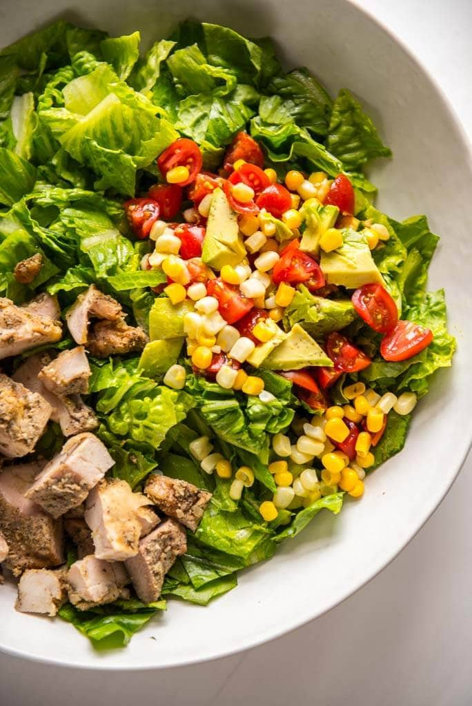 grilled chicken taco salad in white bowl with corn salsa