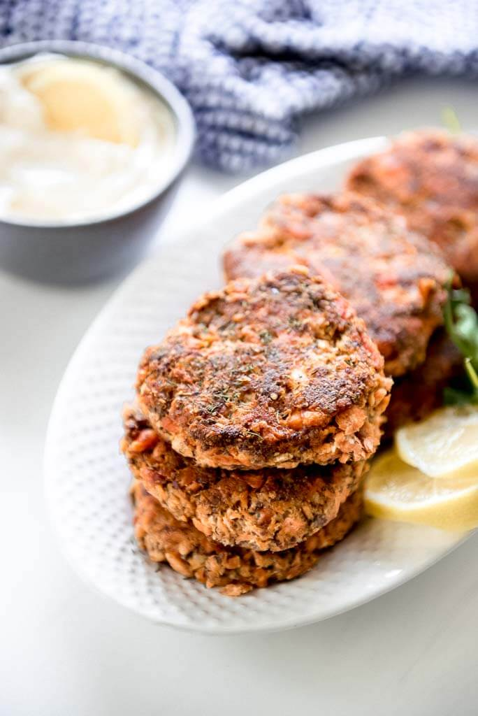 6 fresh salmon patties on white oval platter with a side of mayo and lemon