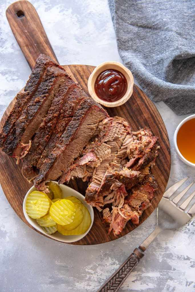 brisket with pickles and sauce on cutting board