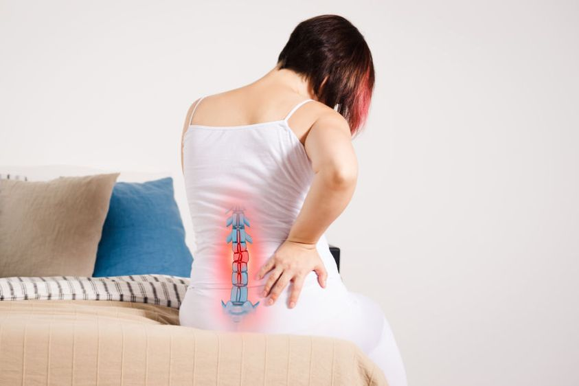 Pain in the spine, woman with backache at home, injury in the lower back