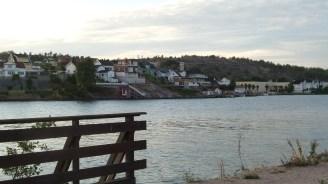 Häuser am Hang auf der anderen Seite eines breiten Flusses.