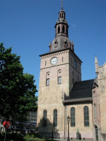Rötliche Steinkirche mit schlichten Glockentrum am Eingang