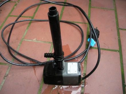 Rechteckiger Motor mit einem Rohr darauf, aus dem im Teich das Wasser strömt. Das Kabel liegt zusammengerollt hinter der Pumpe