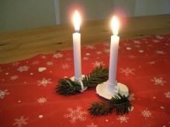 Zwei selbstgemachte Kerzenständer für kleine Kerzen, verziert mit Tannengrün. Die Kerzen brennen