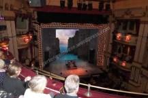 Blick von oben auf die Bühne, auf der eine Kulisse von Häusern und am Ende Meer zu sehen ist