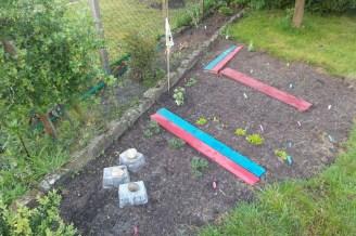 Gemüsebeetansicht von oben. Mit bunten Weghölzern und z. T. Plastikabdeckungen.