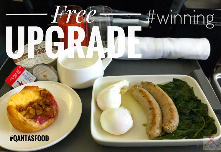 Qantas free business class upgrade breakfast. Pork sausages, poached eggs and wilted spinach with a Danish pastry and sweetened Greek yoghurt.