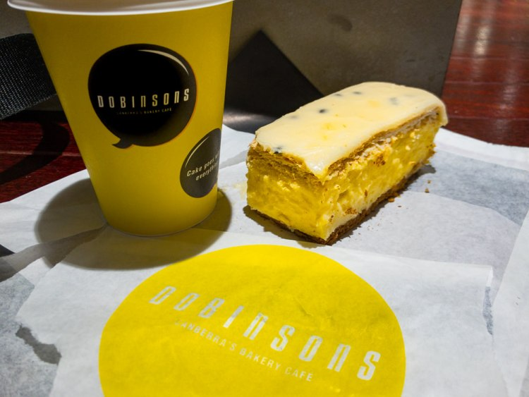 This is a photograph of a cup of coffee and a vanilla slice from Dobinsons Westfield Belconnen.