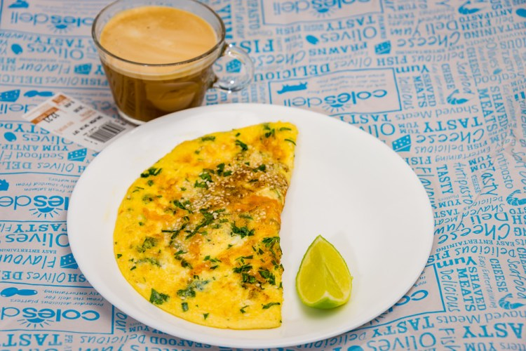 This is a photograph of Sunday breakfast. Coon cheese and sesame seed omelet served with a slice of lime and a caramel cream coffee. I love lime juice.