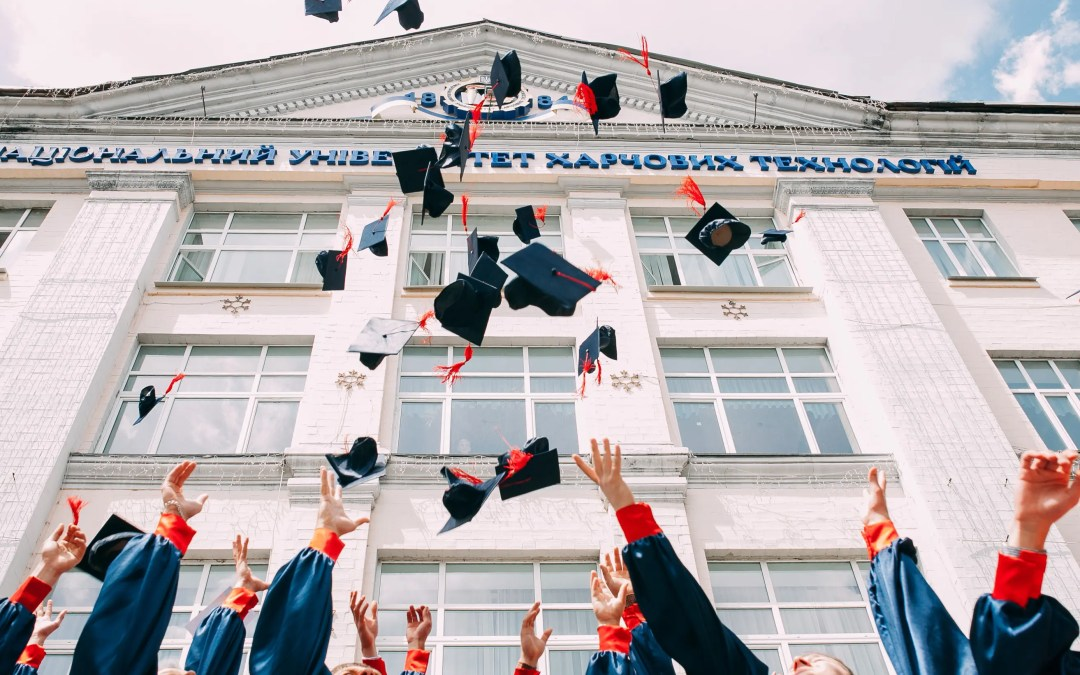 phd graduates in academia for a job in the private sector throw their caps in the air at graduation